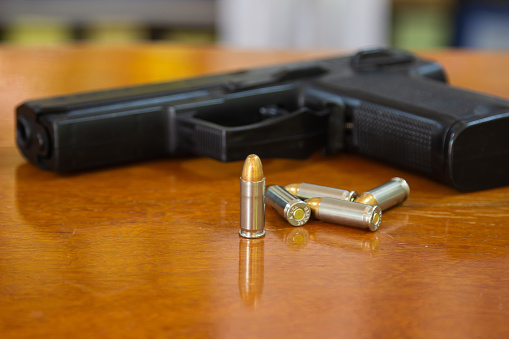 A black handgun on a table next to bullets