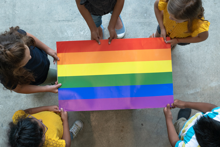 Youth holding a rainbow pride poster
