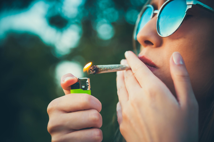 closeup of a teen lighting a marijuana cigarette